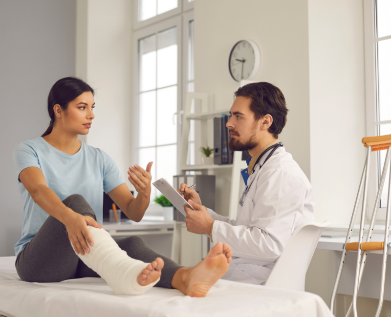 physiatrist speaking to female patient with leg in cast