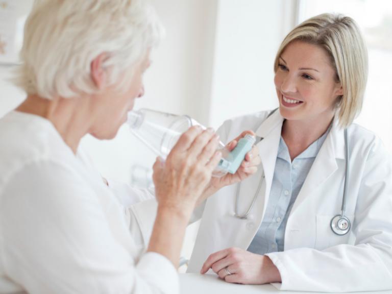 Pulmonologist Teaching Elderly Patient How to use Inhaler