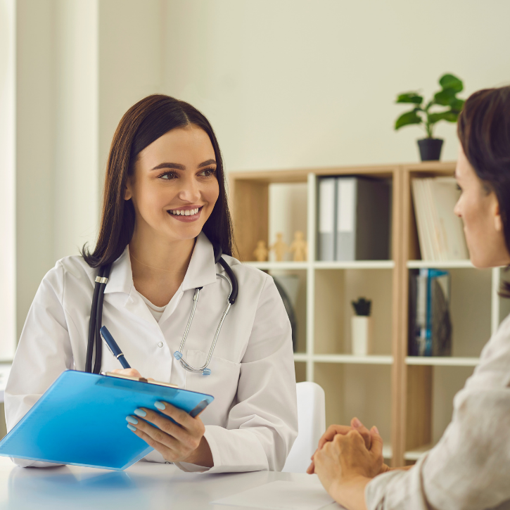Sexual Health Doctor smiling and holding a blue clipboard while talking to a female patient