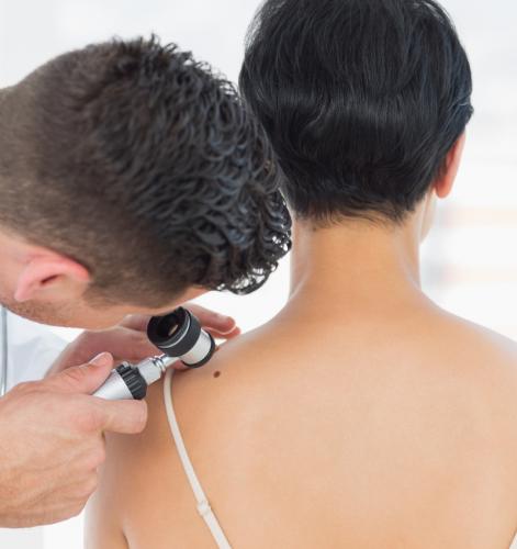 dermatologist inspecting female patient shoulder skin